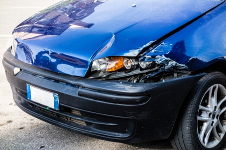 anterior: a small blue car damaged in the anterior left lights Stock Photo