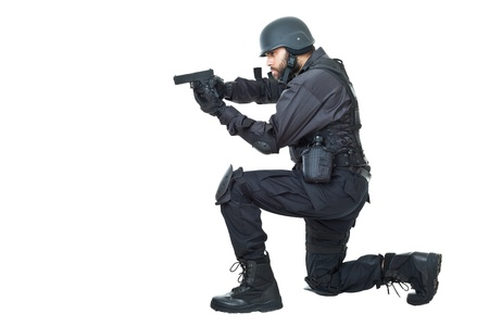 a swat agent wearing a bulletproof vest and aiming with a gun photo