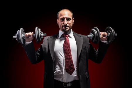 een serieuze zakenman draagt een pak en het opheffen van twee zware gewicht