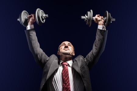 hombre fuerte: un hombre de negocios grave, llevaba un traje y el levantamiento de dos peso pesado Foto de archivo