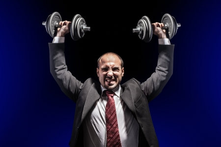 exertion: a serious businessman wearing a suit and lifting two heavy weight