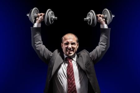 Een serieuze zakenman draagt ??een pak en het opheffen van twee zware gewicht Stockfoto - 20927028