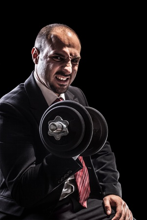 a serious businessman wearing a suit and lifting two heavy weight photo