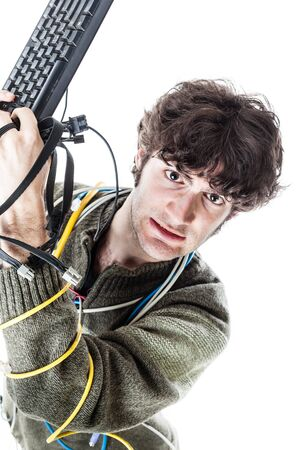 cable tangle: a casual guy with tangled cables and a keyboard struggeling to get computer assistance. isolated on white