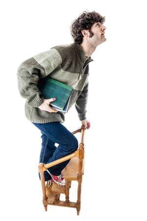 an handsome guy, maybe a student, in casual clothing clambering on a small wooden library ladder. isolated on white photo