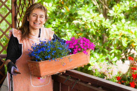 a mature woman making some gardening on a balcony Stock Photo