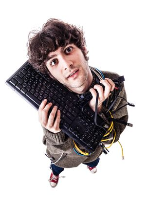 a casual guy with tangled cables and a keyboard struggeling to get computer assistance. isolated on white photo