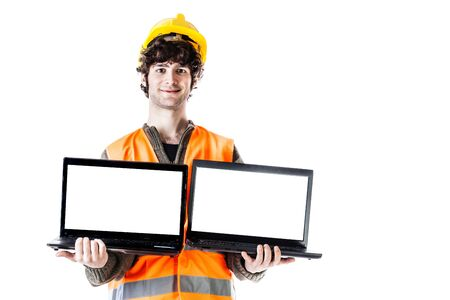 an engineer or an architect wearing a helmet and a reflective vest and holding two laptops with blank screen. Isolated on white photo