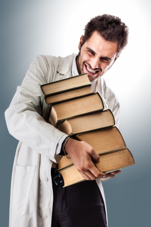 scientific literature: a young and handsome doctor or medical student carrying a pile of ancient book Stock Photo