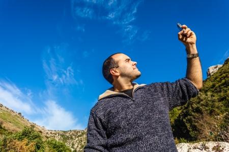 un hombre que trataba de captar la señal en su teléfono móvil Foto de archivo