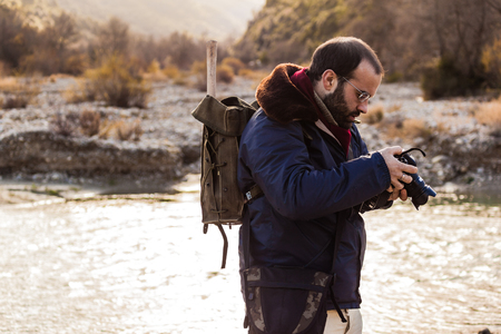 a man hiking and looking at the screen of a digital single lens reflex Stock Photo - 23336887