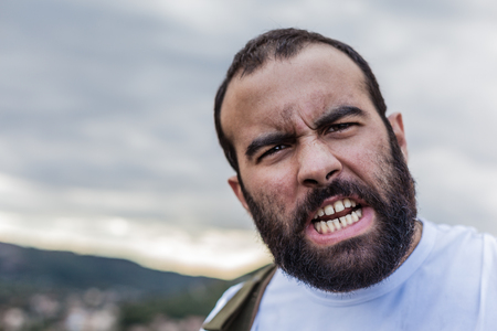 portrait of a crazy man showing the teeth in anger photo
