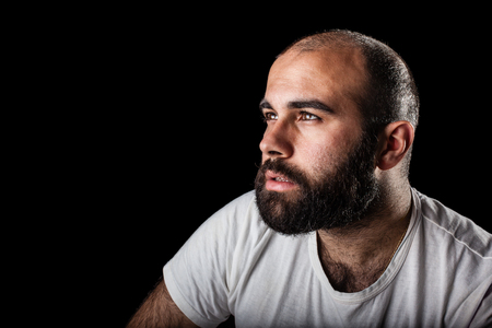 a masculine bearded man isolated over a black background photo