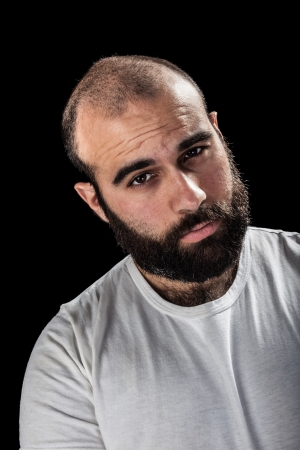 a masculine bearded man isolated over a black background
