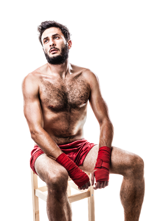 recuperating: a very muscular young boxer with red trunks and hand wraps isolated over white background Stock Photo