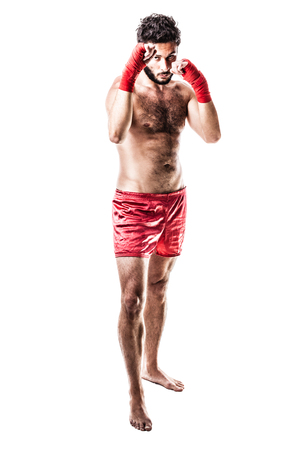 a very muscular young boxer with red trunks and hand wraps isolated over white background Stock Photo