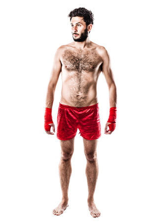 a very muscular young boxer with red trunks and hand wraps isolated over white background photo