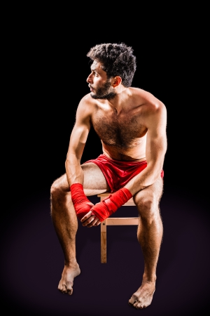 bare foot: a very muscular young boxer with red trunks and hand wraps over a dark background