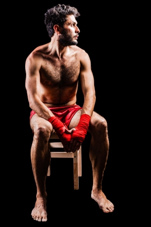 a very muscular young boxer with red trunks and hand wraps over a dark background photo