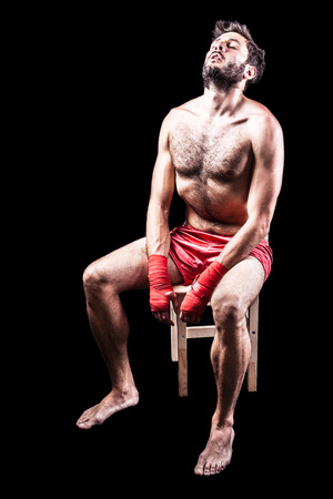recuperating: a very muscular young boxer with red trunks and hand wraps over a dark background