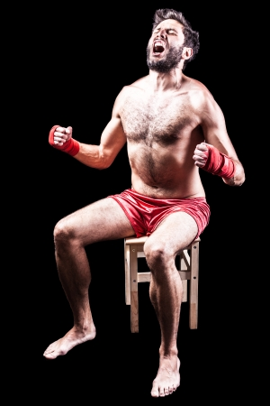 bawl: a very muscular young boxer with red trunks and hand wraps over a dark background
