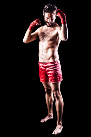 fiercely: a very muscular young boxer with red trunks and hand wraps over a dark background