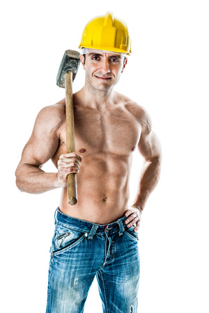 a very muscular and handsome manual worker with a sludgehammer and a yellow helmet isolated over white photo