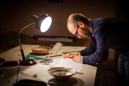 archeologist: an archeologist examining some ancient crocks on a desk Stock Photo