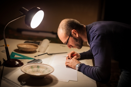 archeologist: an archeologist examining some ancient crocks on a desk Stock Photo