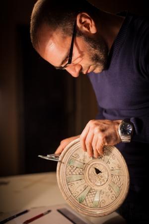 an archeologist examining some ancient crocks on a desk Banco de Imagens