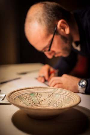 an archeologist examining some ancient crocks on a desk