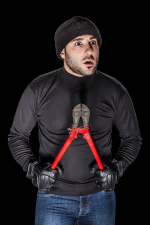 a burglar wearing black clothes holding huge wire cutters over black background Stock Photo - 23423017