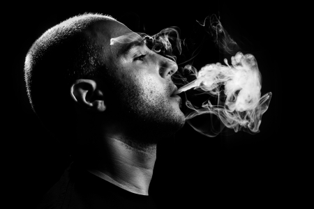 man smoking: dark and sullen shot of a young man smoking over a black background