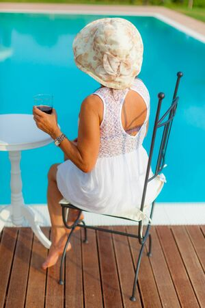 a beautiful mature woman having a dring at the pool side photo