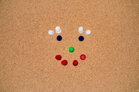 colourful thumbtacks on a cork clipboard arrangen in a smiley photo