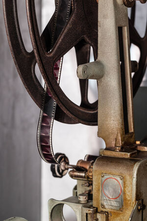 16mm: detail of an old and rusty cinema projector with film roll