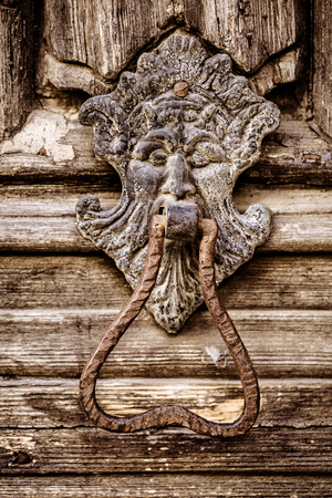 an old and rusty lion shaped door knocker on an antique wooden door photo