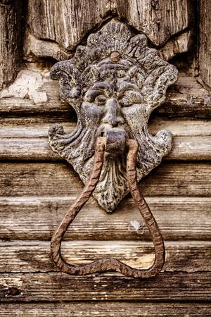 doorknocker: an old and rusty lion shaped door knocker on an antique wooden door Stock Photo
