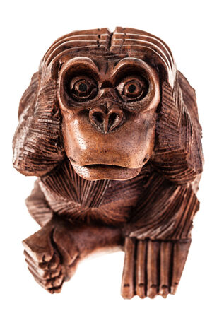 monkey nuts: a wooden monkey sculpture isolated over a white background