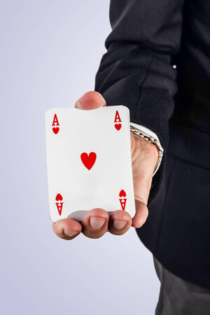 an elegant young businessman holding a ace of hearts in his hand photo