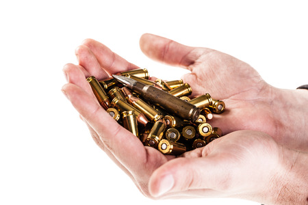 warheads: a heap of 9mm pistol bullets holded by human hands isolated over a white backgrounds