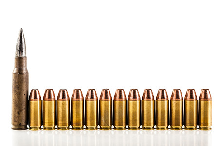 armament: a lot of 9mm bullets arranged in a row and isolated over a white background Stock Photo