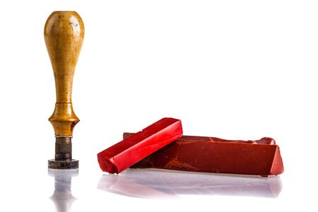 signet: red sealing wax sticks, a wooden seal and an envelope isolated over a white background Stock Photo