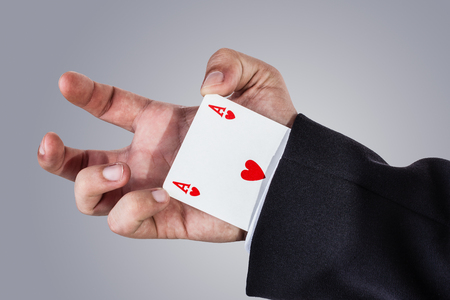 an elegant young businessman making card tricks with poker cards photo