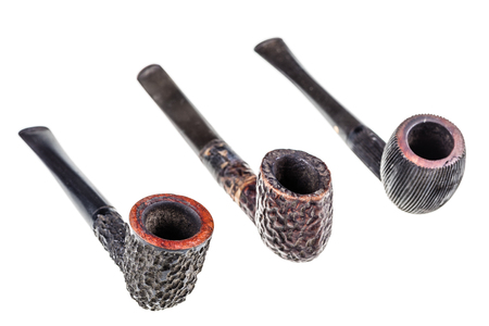 three rustic tobacco pipes isolated over a white background photo
