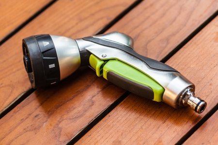 a revolver watering nozzle on a wooden table in the backyard Stock Photo - 23397939