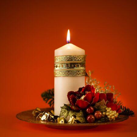 ornated: un bellissimo ornato centrotavola di Natale con una candela accesa in bianco Archivio Fotografico
