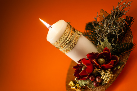 ornated: un bellissimo centrotavola di Natale ornato con una candela bianca accesa