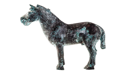 an ancient statuette depicting a horse isolated over a white background photo