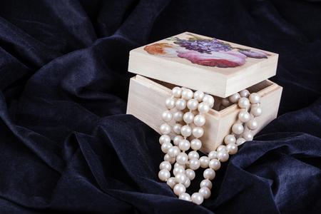 ornated: una scatola di legno ornato contenente una bella collana di perle